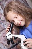 Meisje op zoek door een microscoop — Stockfoto