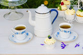 Tea with cupcakes in a vintage teapot — Stock Photo