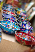 Small colorful pottery bowls in a row — Stock Photo