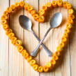 Love heart from orange peels with crossed spoons - Stok fotoğraf