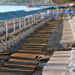 Empty sunbeds and umbrellas on a hotel beach — Stock Photo