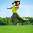 Young woman jumping on a green meadow — Stock Photo #25406949