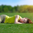 Young woman lying on a green meadow — Stock Photo #25407239