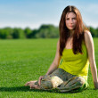 Young beautiful brunette woman sitting on green meadow. — Stock Photo #25406313