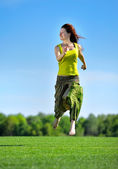 Young woman running on a green meadow — Stock Photo