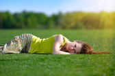 Young woman lying on a green meadow — Stock Photo