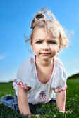 Baby girl crawling on the green grass in the park — Stock Photo