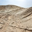 Sand hills over blue sky with car tires footprint — Stock Photo