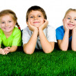 Boy and girls lying on a green grass — Stock Photo