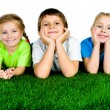 Boy and girls lying on a green grass - Stock Photo