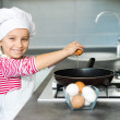 Little girl cracking an egg - Stock Photo