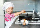 Little girl cracking an egg — Stock Photo
