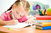 Little girl is writing — Stockfoto