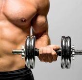 Powerful muscular man lifting weights — Stok fotoğraf