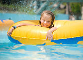 Little girl sitting on inflatable ring — Stock Photo