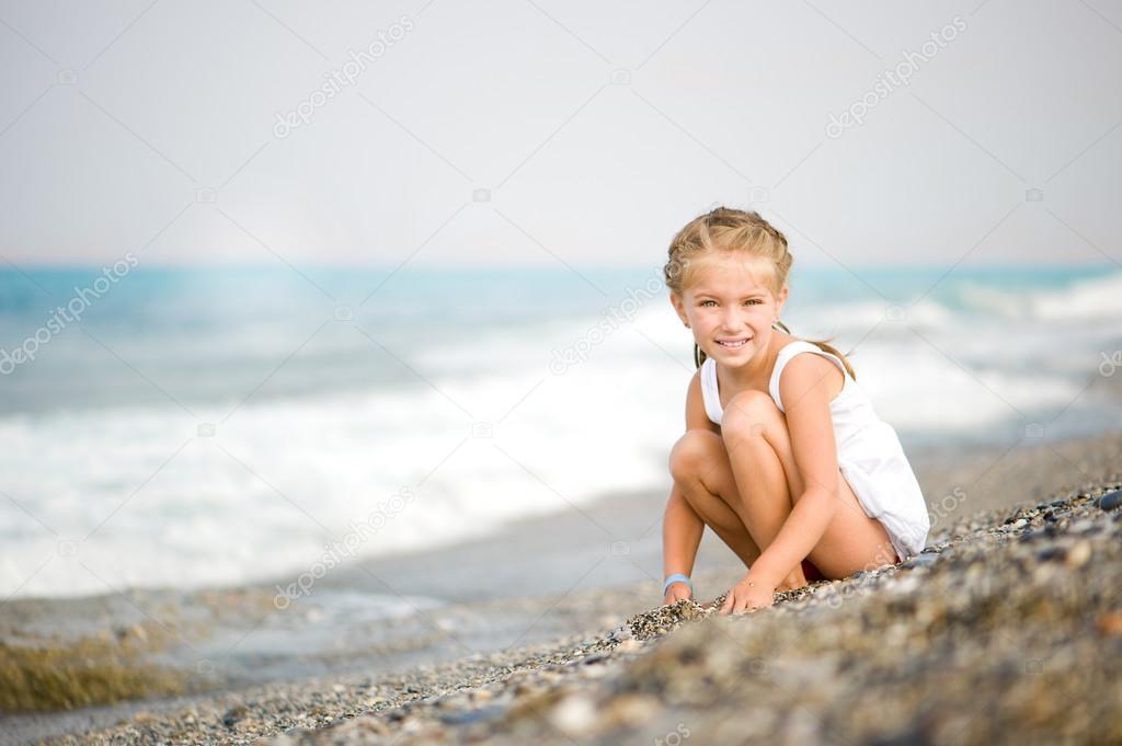 在她的手在海滩上的小石子的小女孩 — 照片作者 tan4ikk