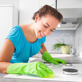 Woman cleans the kitchen — Stock Photo