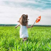 Girl with a windmill in hand — Zdjęcie stockowe