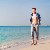 Strong young man at beach — Stock Photo