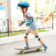 Little girl with a helmet riding on skateboard — Stock Photo