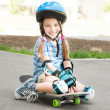 Little girl sitting on a skateboard — Stock Photo