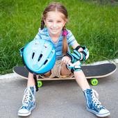 Bir kaykay üzerinde oturan küçük kız — Stok fotoğraf