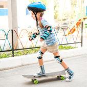 Little girl with a helmet riding on skateboard — Stock Photo