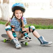 маленькая девочка, сидя на скейтборде — Стоковое фото