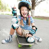 Little girl sitting on a skateboard — Stock Photo