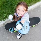 Bambina seduta su uno skateboard — Foto Stock
