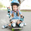 Little girl sitting on a skateboard — Stock Photo #28436809