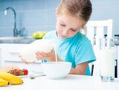 Little girl pouring milk — Stock Photo