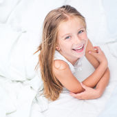 Six year old girl in a white bed — Stock Photo