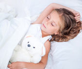 Little girl in the bed with teddy bear — Stock Photo