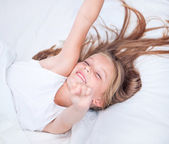 Girl lying in white bed — Stock Photo