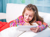 Cute little girl with the tablet — Stock Photo