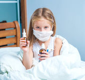 Little girl holding a cough syrup bottle — Stock Photo
