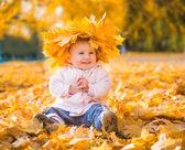 Cute little girl among maple leaves — Stock Photo
