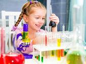 Little girl with flasks for chemistry — Stok fotoğraf