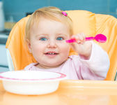 One year old girl in a highchair for feeding — Stock Photo