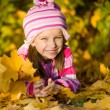 Smiling cute girl against the leaves — Stock Photo