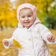 Little girl among autumn leaves — Foto Stock