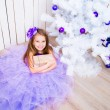 Little girl with a gift   near Christmas tree — Stock Photo