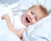 Baby lying in a white bed — Foto de Stock