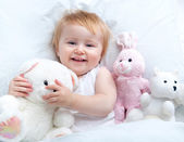 Baby lying in a white bed — Stock Photo