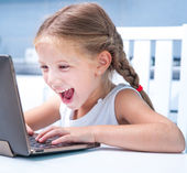 Little girl with her computer — Stock Photo