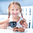 Cute little girl drinking tea with cookies — Stock Photo