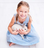 Cute little girl a white rabbit — Stok fotoğraf
