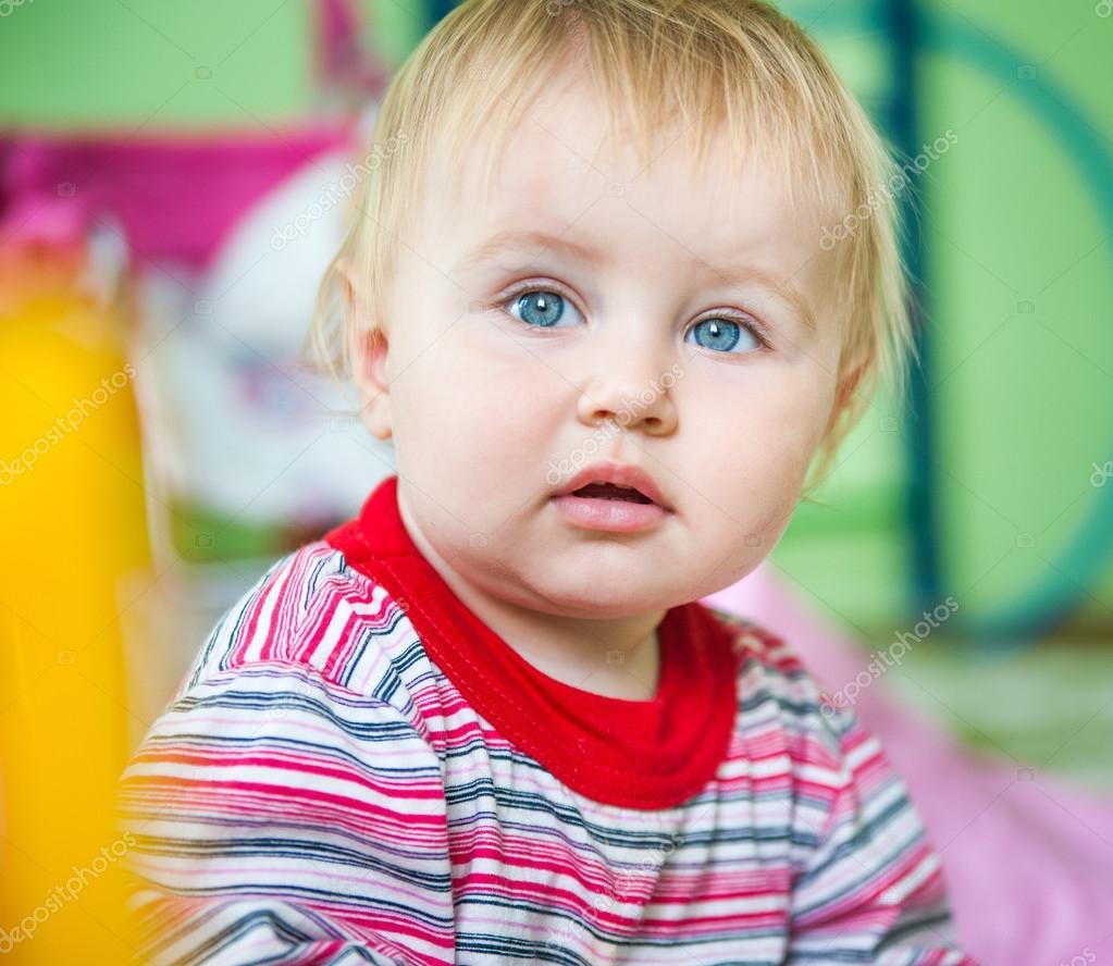 可爱蓝眼睛的孩子在明亮苗圃特写– 图库图片
