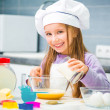 Cute little girl in the kitchen preparing cookies — Stock Photo #38472283